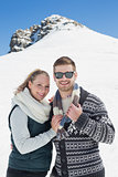 Smiling couple in warm clothing in front of snowed hill