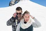 Happy couple in warm clothing in front of snowed hill
