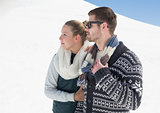 Couple in warm clothing on snow covered landscape