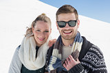 Smiling couple in warm clothing on snow covered landscape