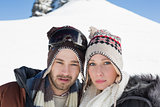 Couple in woolen hats on snow covered landscape