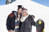 Portrait of a smiling couple in jackets with ski board