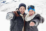 Cheerful couple in jackets pointing at camera on snow covered landscape