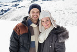 Couple in warm clothing standing on snowed landscape