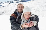 Couple with cupped hands on snowed landscape