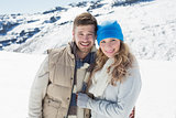 Loving couple in warm clothing on snow covered landscape