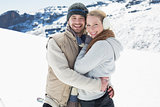 Loving couple in warm clothing on snowed landscape