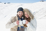 Cheerful couple in warm clothing with coffee cups on snowed landscape