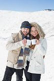 Couple in warm clothing with coffee cups on snowed landscape