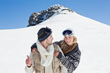 Couple in jackets and ski goggles against snowed hill
