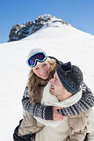 Man piggybacking cheerful woman against snowed hill