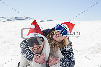 Close up of a cheerful couple in ski goggles on snow