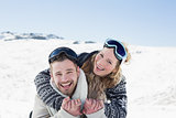 Cheerful couple with ski goggles on snow