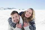 Close up of a cheerful couple holding hands on snow