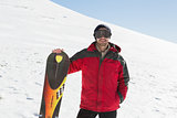 Smiling man with ski board standing on snow