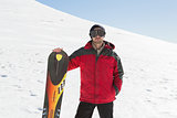 Portrait of a serious man with ski board standing on snow
