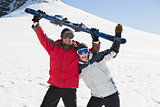 Cheerful couple holding up ski board on snow