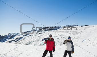 Couple carrying ski boards while walking on snow