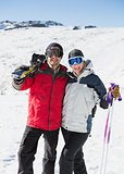 Portrait of a cheerful couple with ski boards on snow