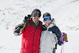 Portrait of a happy couple with ski boards on snow
