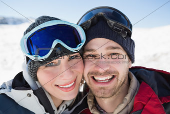 Close up of a cheerful couple with ski goggles on snow