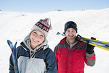 Portrait of a smiling couple with ski boards nn snow