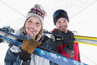 Close up of a smiling couple with ski boards on snow