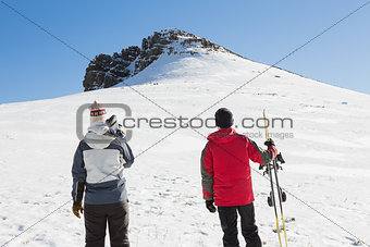 Rear view of a couple with ski boards on snow