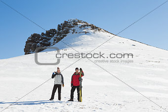 Full length of a couple with ski boards standing on snow