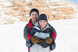 Portrait of a happy man embracing woman from behind on snow