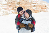 Happy man embracing woman from behind on snow