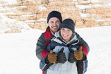 Happy loving couple gesturing thumbs up on snow