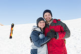 Happy loving couple with ski board on snow in background
