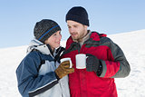 Couple in warm clothing with coffee cups on snow
