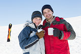 Couple having coffee with ski board in snow