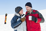 Loving couple having coffee with ski board in snow