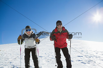 Skiers on snow covered landscape against blue sky