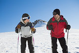 Smiling couple with ski poles on snow
