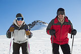 Portrait of a smiling couple with ski poles on snow