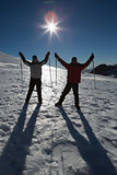 Silhouette couple raising hands with ski poles on snow