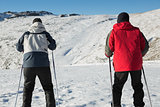 Rear view of a couple with ski poles on snow