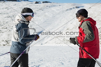 Side view of a smiling couple with ski poles on snow