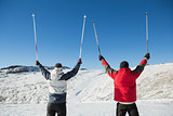 Rear view of a couple raising ski poles on snow