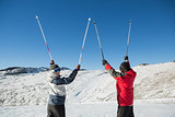 Rear view portrait of a couple raising ski poles on snow