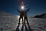 Silhouette couple with hands raised on snow against sun and blue sky