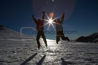 Silhouette couple jumping on snow against sun and blue sky