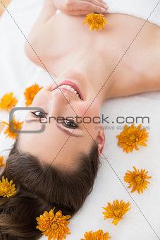 Brunette lying on massage table in beauty salon