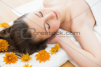 Brunette lying on massage table in beauty salon