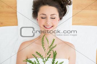 Brunette lying with leaves in beauty salon