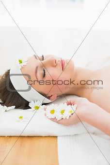 Beautiful woman with eyes closed lying on massage table